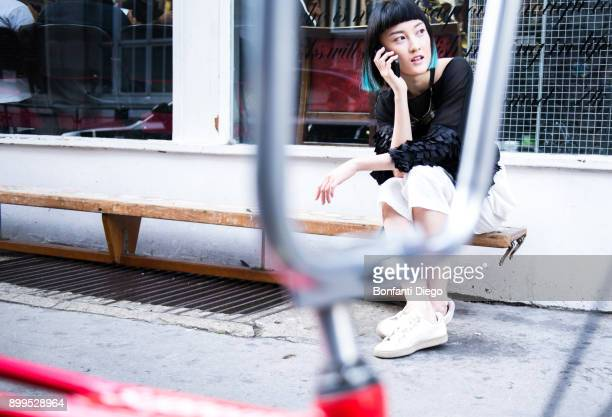 young stylish woman sitting outside shop making smartphone call - vita cittadina foto e immagini stock