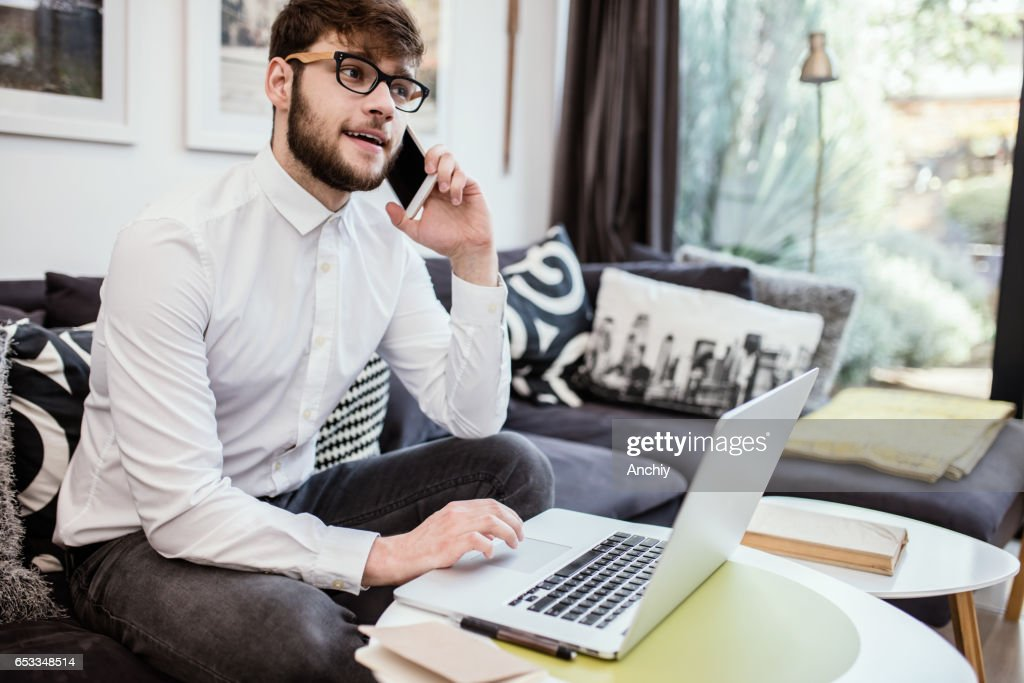 Young successful businessman talking on smartphone while getting information from laptop. : Stock Photo