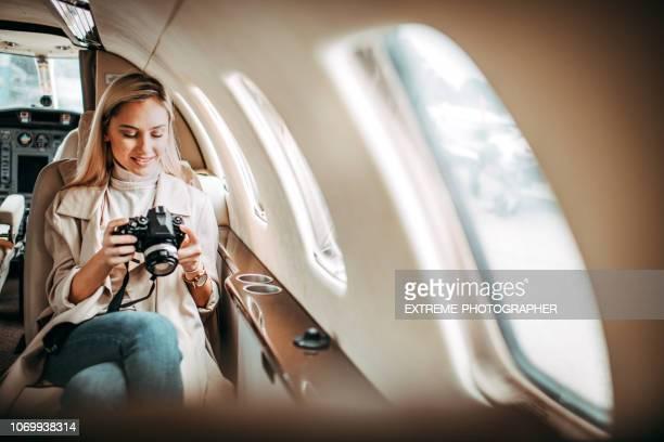 jonge succesvolle zakenvrouw zit in een prive-jet - voertuiginterieur stockfoto's en -beelden