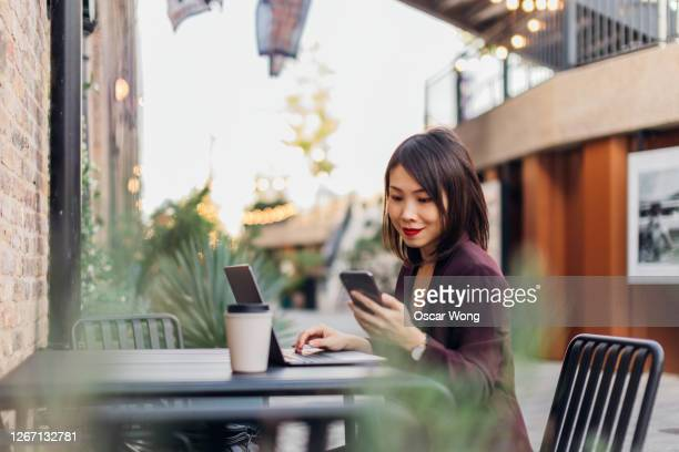 young successful female freelancer working at an industrial style outdoor cafe - using laptop stock pictures, royalty-free photos & images