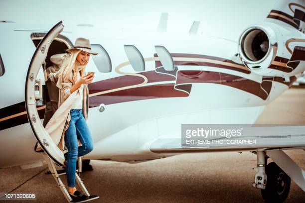 young successful woman exiting a private airplane - millionnaire stock pictures, royalty-free photos & images