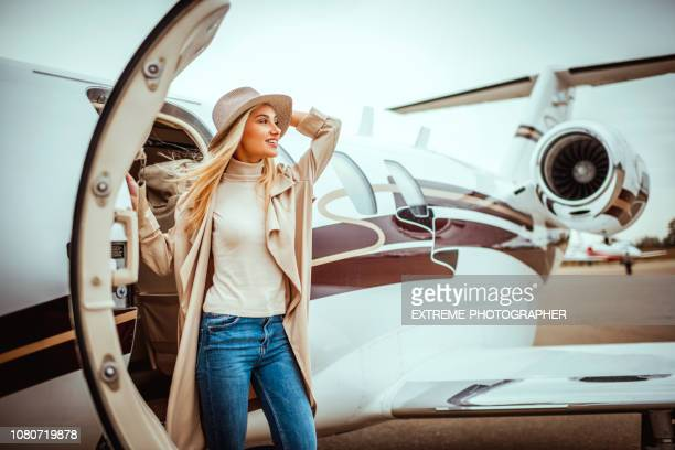 young successful woman exiting a private airplane - disembarking stock pictures, royalty-free photos & images