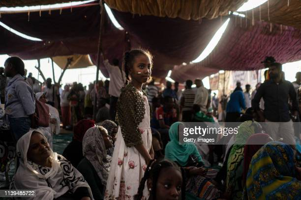 Young Sudanese girl is watching protestors pass by during the ongoing protest against the military junta on April 26, 2019 in Khartoum, Sudan. After...