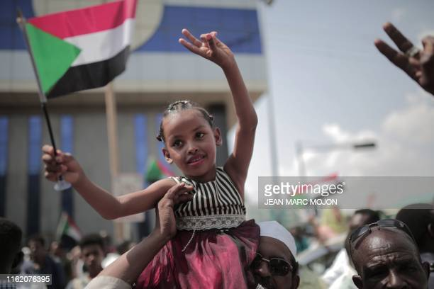 A young Sudanese girl waves a national flag as people celebrate outside the Friendship Hall in the capital Khartoum where generals and protest...