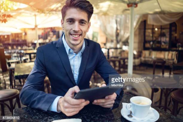 Young suited male browsing on his tablet