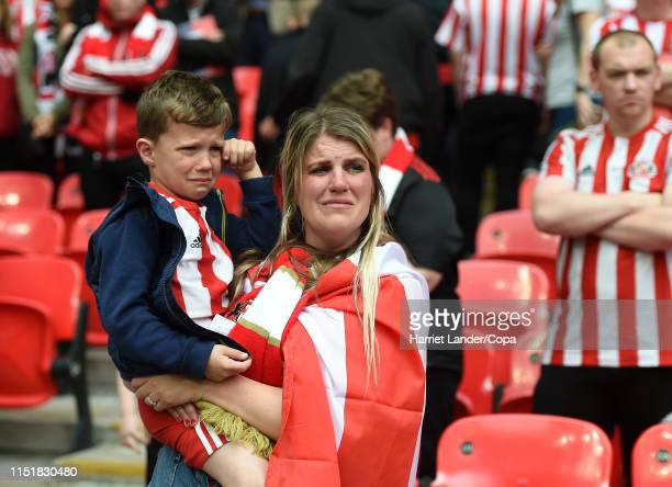 Young Sunderland fan and his guardian look dejected following their team's defeat in the Sky Bet League One Play-off Final match between Charlton...