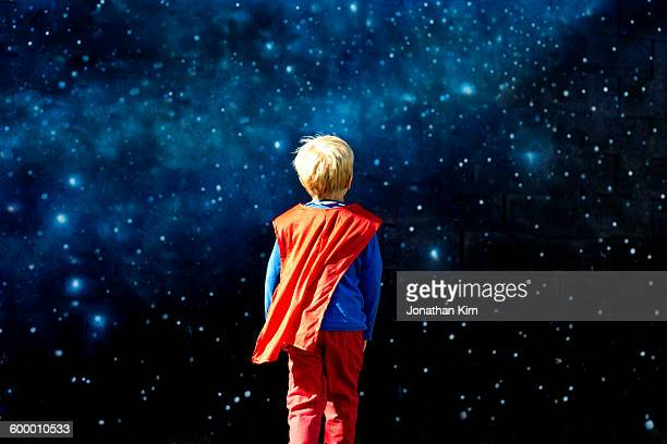 Young super hero against a field of stars.