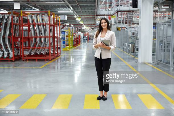 young supervisor with tablet pc in car factory - yellow blazer stock photos and pictures