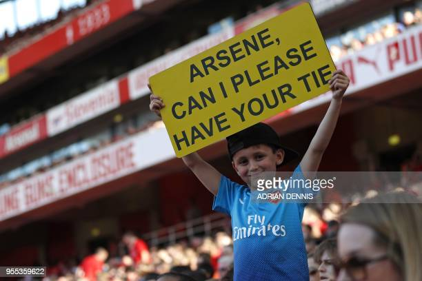 A young supporter holds up a sign asking for Wenger's tie during the English Premier League football match between Arsenal and Burnley at the...