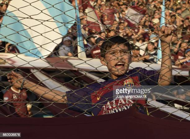 A young supporter of Argentina's Lanus wearing a Barcelona FC jersey shouts while waiting for the start of the Copa Libertadores 2017 final football...