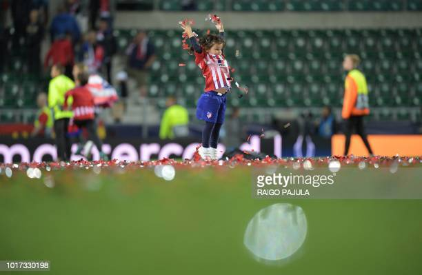 A young supporter of Atletico Madrid plays with confetti after Atletico Madrid won the UEFA Super Cup football match Atletico de Madrid vs Real...