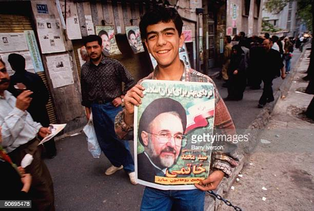 Young supporter of moderate cleric Mohammed Khatami w. Election campaign poster picturing surprise front-runner presidential candidate poised on...