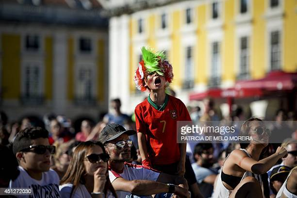 A young supporter of Portugal's national football team reacts as he watches the FIFA World Cup 2014 match Portugal vs Ghana on a screen at Terreiro...