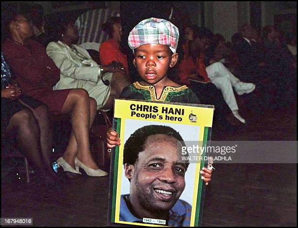 A young supporter of slain South African Communist Party chief Chris Hani holds a portrait of Hani at an amnesty hearing of his murderers in Pretoria...