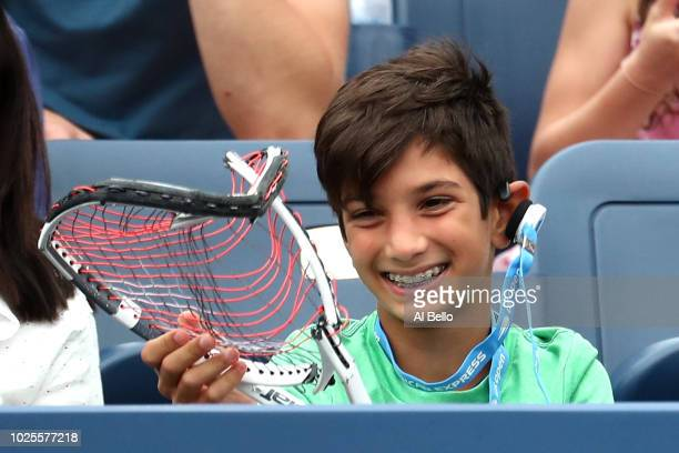 A young supporter recieves a broken raquet from Dominic Thiem of Austria during hie men's singles third round match against Taylor Fritz of the...