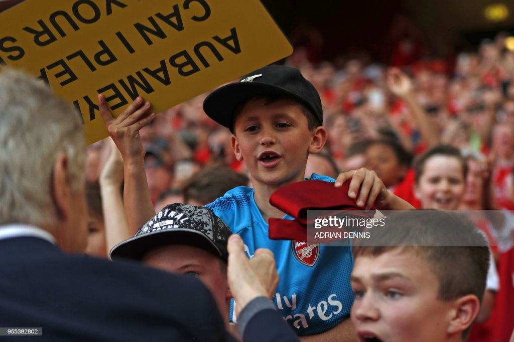 A young supporter, seven year old Luca Iacurti is handed a tie which Arsenal's French manager Arsene Wenger was wearing after the English Premier League football match between Arsenal and Burnley at the Emirates Stadium in London on May 6, 2018. - Arsene Wenger bids farewell to a stadium he helped to build in more ways than one when he leads Arsenal at the Emirates for the final time at home to Burnley on Sunday. Wenger's final season after 22 years in charge is destined to end in disappointment after Thursday's Europa League semi-final exit. (Photo by Adrian DENNIS / AFP) / RESTRICTED TO EDITORIAL USE. No use with unauthorized audio, video, data, fixture lists, club/league logos or 'live' services. Online in-match use limited to 75 images, no video emulation. No use in betting, games or single club/league/player publications. /