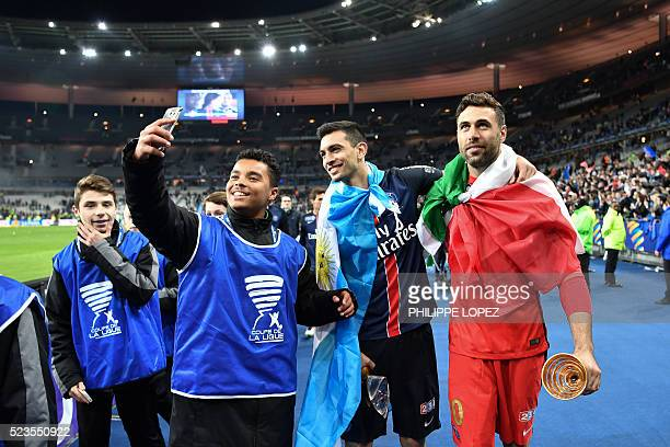 A young supporter takes a selfie photo with Paris SaintGermain's Italian goalkeeper Salvatore Sirigu and Paris SaintGermain's Argentinian midfielder...