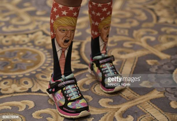 TOPSHOT A young supporter wears socks with the image of Republican presidential nominee Donald Trump ahead of his press conference at the Trump...
