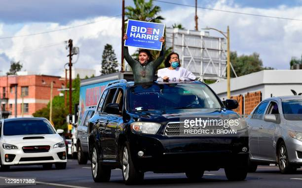 Young supporters cheer from their car holding a Biden-Harris placard as people take to the streets in Los Angeles on November 7, 2020 to celebrate...
