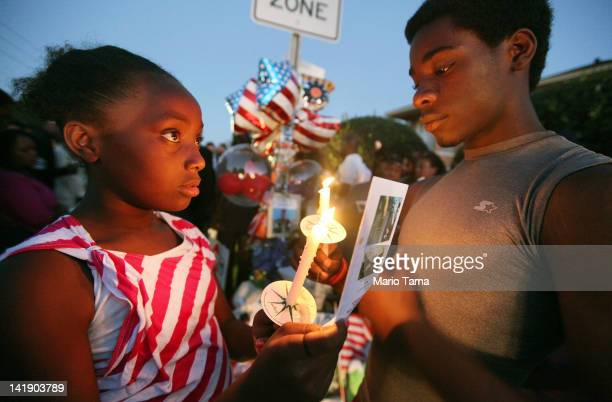 Young supporters gather during a candelight vigil at a memorial to Trayvon Martin outside The Retreat at Twin Lakes community where Trayvon was shot...