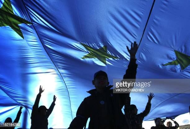 Young supporters of Belarus's opposition carry a European Union flag as they walk along a street during the 'European march' rally in Minsk 14...