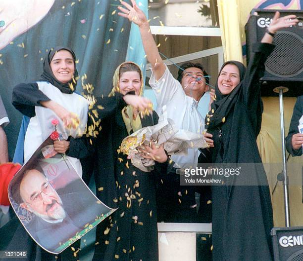 Young supporters of incumbent Iranian President Mohammed Khatami throw flowers into the crowd during a rally to celebrate Khatami''s projected...