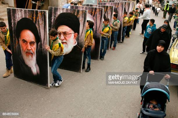 Young supporters of Lebanon's militant Shiite Hezbollah movement carry portraits of the founder of Iran's Islamic Republic Ayatollah Ruhollah...