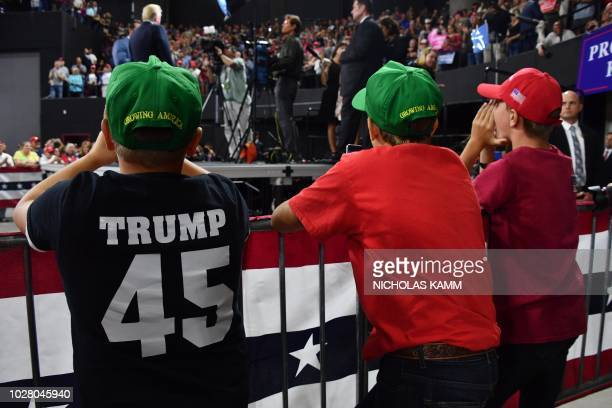 Young supporters of US President Donald Trump cheer and wear caps reading Growing America as Trump arrives to a Make America Great Again rally in...