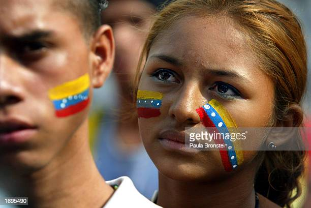 Young supporters of Venezuelan President Hugo Chavez listen to a speech as they attend a rally December 19 2002 in Caracas Venezuela The country is...
