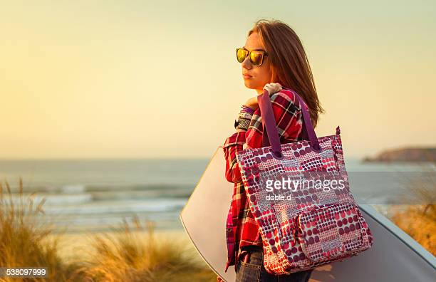 Young surfer girl holding beach bag and bodyboard
