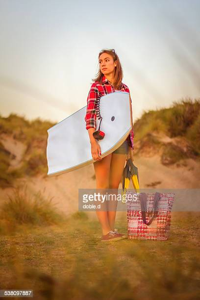 Young surfer girl holds bodyboard and fins on sand