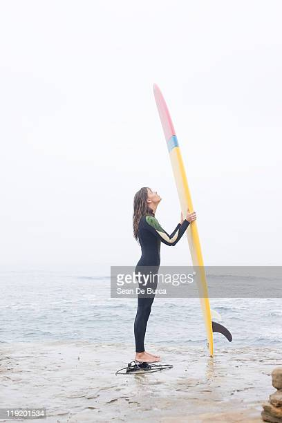 Young surfer looking up at surfboard.