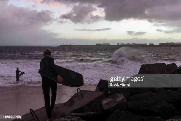 A young surfer makes his way to the rare waves breaking inside Botany Bay on June 04 2019 in Sydney Australia The Bureau of Meteorology issued a...