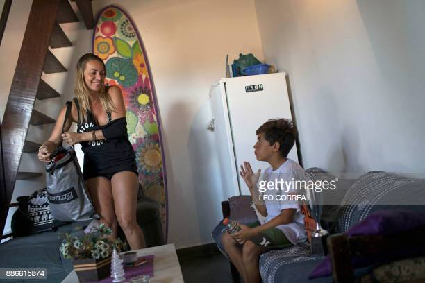 Young surfer Rickson Falcao and his mother Rejane Campos Falcao get ready before heading to Saquarema's beach in Rio de Janeiro state Brazil on...