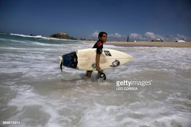 Young surfer Rickson Falcao carries his board after surfing at Saquarema's beach in Rio de Janeiro state Brazil on November 29 2017 Despite its vast...