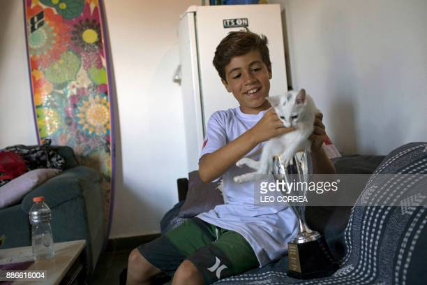 Young surfer Rickson Falcao jokes with his cat and one of his trophies at his house in Saquarema Rio de Janeiro state Brazil on November 29 2017...