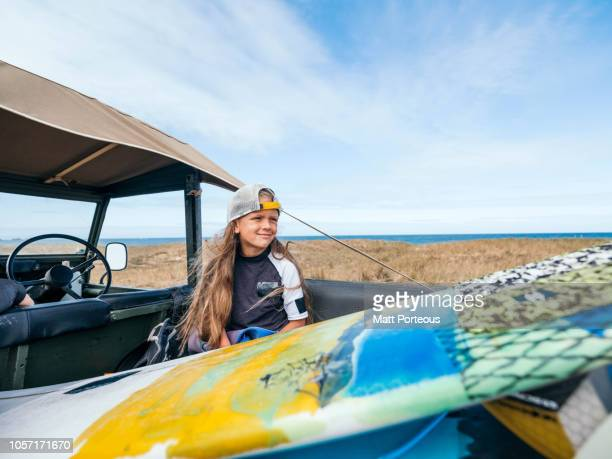 Young surfer sat in jeep