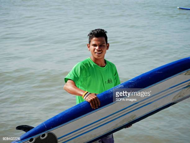 A young surfer seen with his surfing board Young people in the world´s longest sandy beach in Cox´s Bazar Bangladesh decided to throw away prejudices...