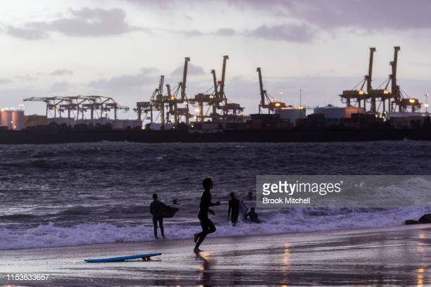 A young surfer sprints to enjoy rare waves breaking inside Botany Bay on June 04 2019 in Sydney Australia The Bureau of Meteorology issued a severe...