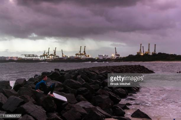 A young surfer waits on the rocks to enter the rare waves breaking inside Botany Bay on June 04 2019 in Sydney Australia The Bureau of Meteorology...