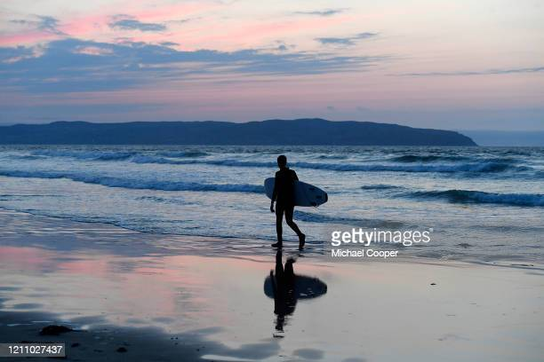 Young surfer walks home after a surf on a deserted Castlerock beach, County Londonderry, Northern Ireland as the sun sets over Donegal, Ireland on...
