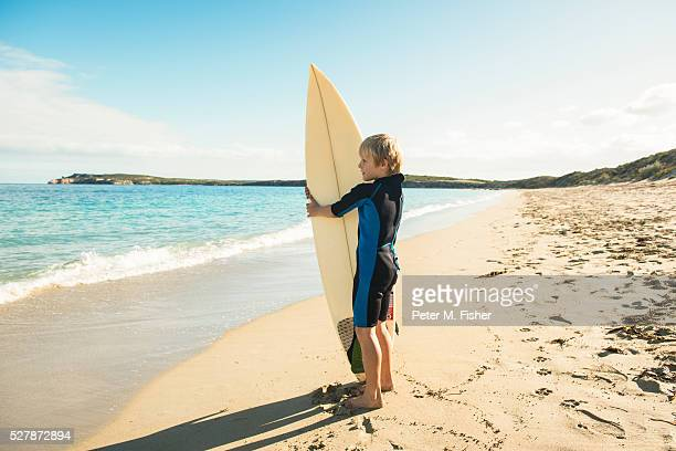 Young surfer (6-7) wearing wetsuit holding surfboard