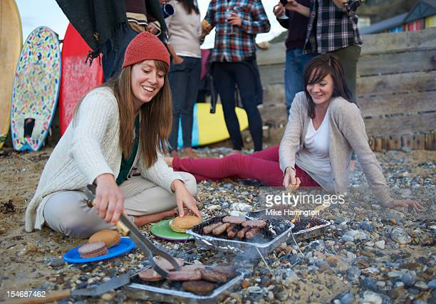 Young surfers cooking on barbecue at beach party.