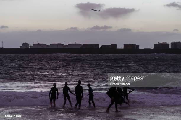 Young surfers enjoy rare surf breaking inside Botany Bay as the sun fades away on June 04 2019 in Sydney Australia The Bureau of Meteorology issued a...