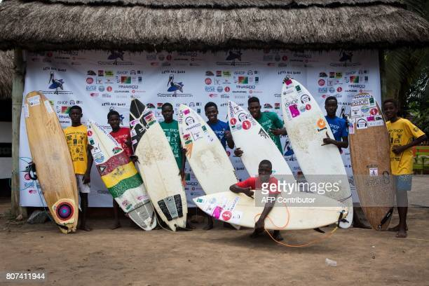 Young surfers pose with their board for a picture during the international surf day competition on Kokrobite Beach Ghana on June 18 2017 The beach...