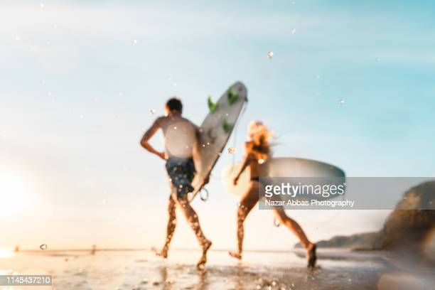 young surfers running towards beach. - nazar abbas photography stock pictures, royalty-free photos & images