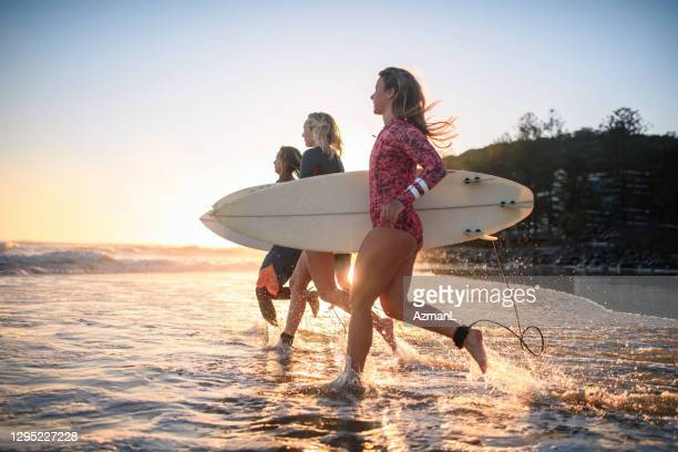 young surfing friends running into water at burleigh heads - coral sea stock pictures, royalty-free photos & images