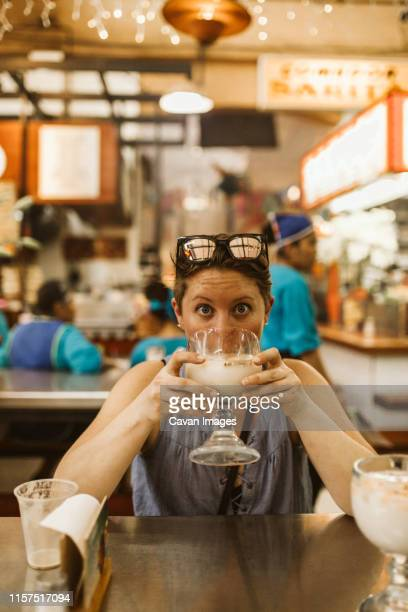 young surprised lady with short hair drinks horchata in mexico - drunk mexican stock pictures, royalty-free photos & images