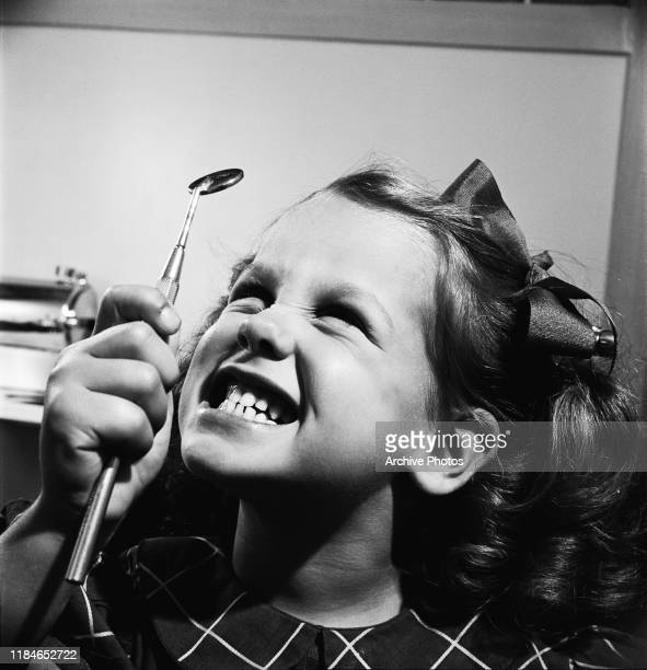 Young Susan May Gorman examines her teeth in a dentist's mirror during a visit to the dentist circa 1955