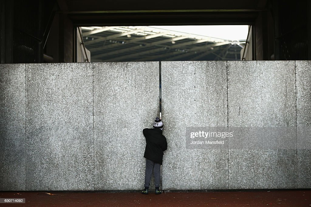 A young Swansea City supporter is seen watching inside the stadium from the gap of the walls prior to the Premier League match between Swansea City and AFC Bournemouth at Liberty Stadium on December 31, 2016 in Swansea, Wales.